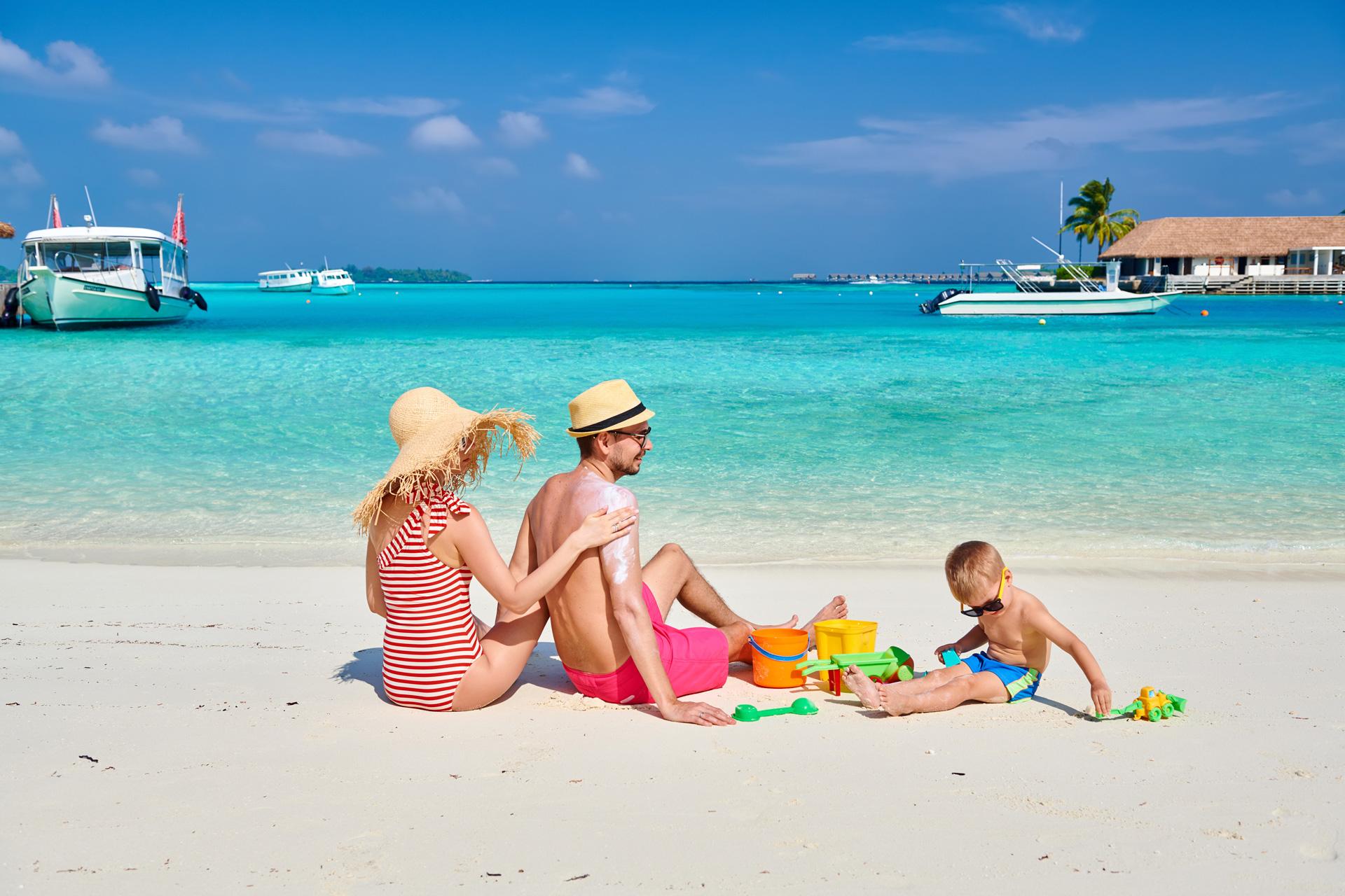Mãe aplicando protetor solar no pai enquanto filho brinca com areia