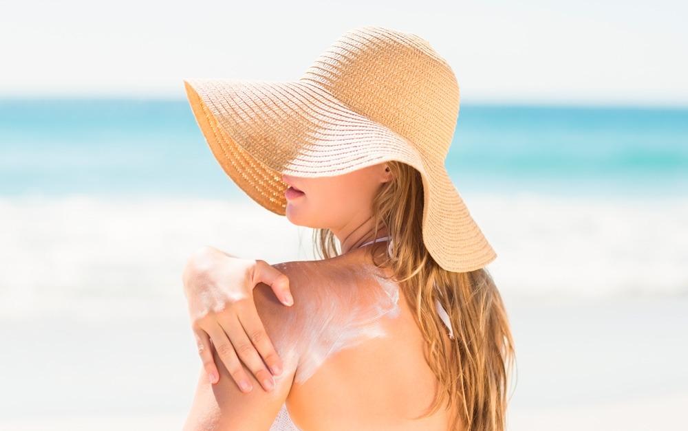 Mulher passando protetor solar Safe Sea na praia