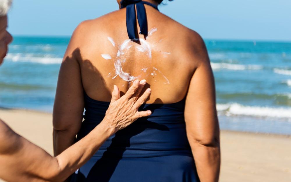 Duas mulheres que são amigas, estão passando o protetor solar Safe Sea para se proteger do sol
