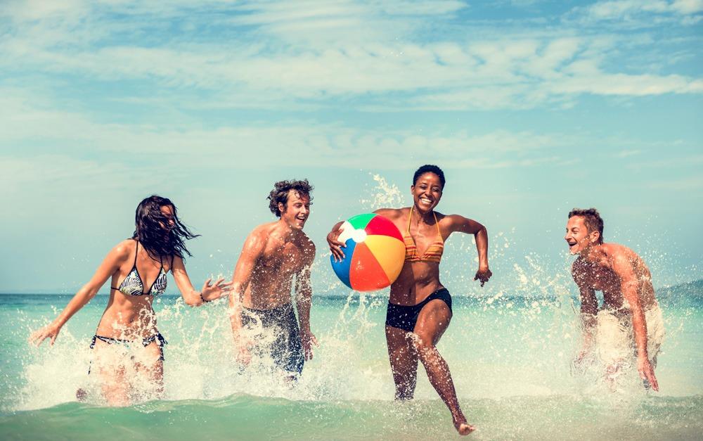 Duas mulheres e dois homens se divertindo no mar, e estão protegidos com Safe Sea®