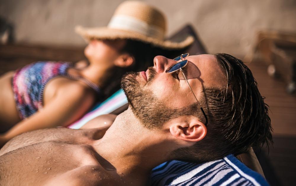 Uma mulher e um homem pegando sol com o protetor solar Safe Sea®