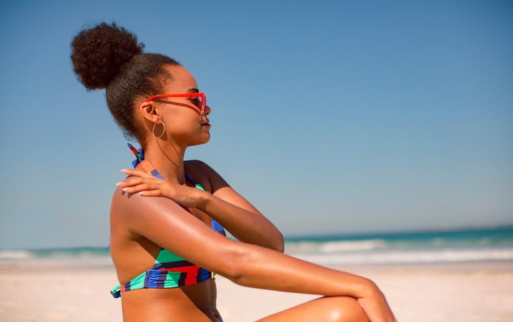 Uma mulher usando protetor solar Safe Sea® na praia