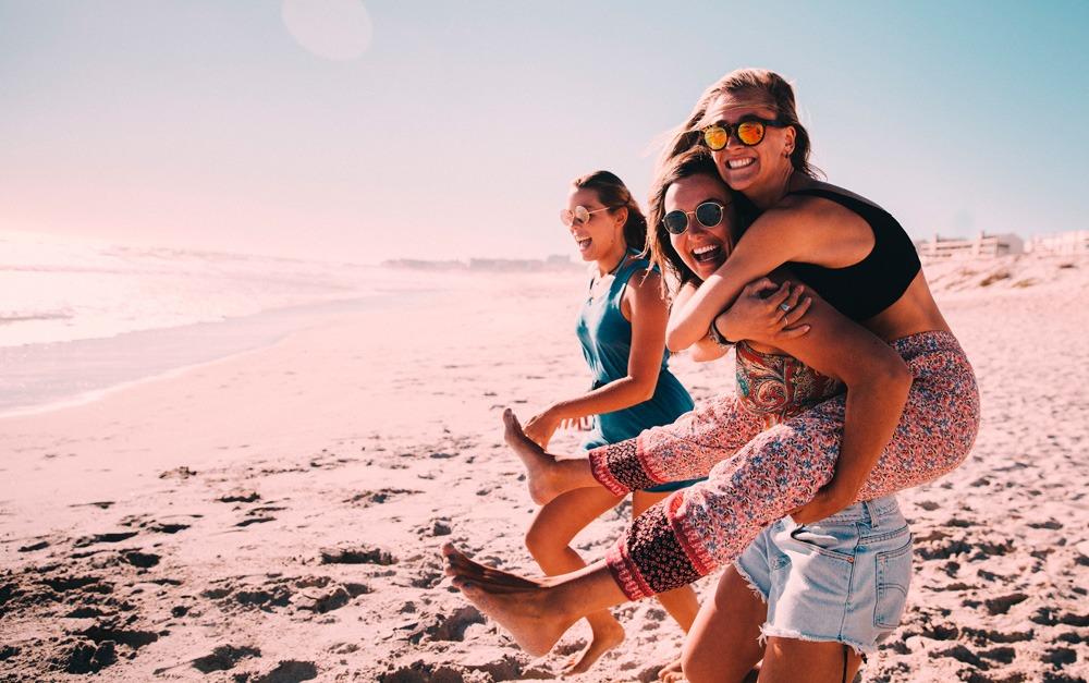 Três mulheres amigas curtindo o nascer do sol