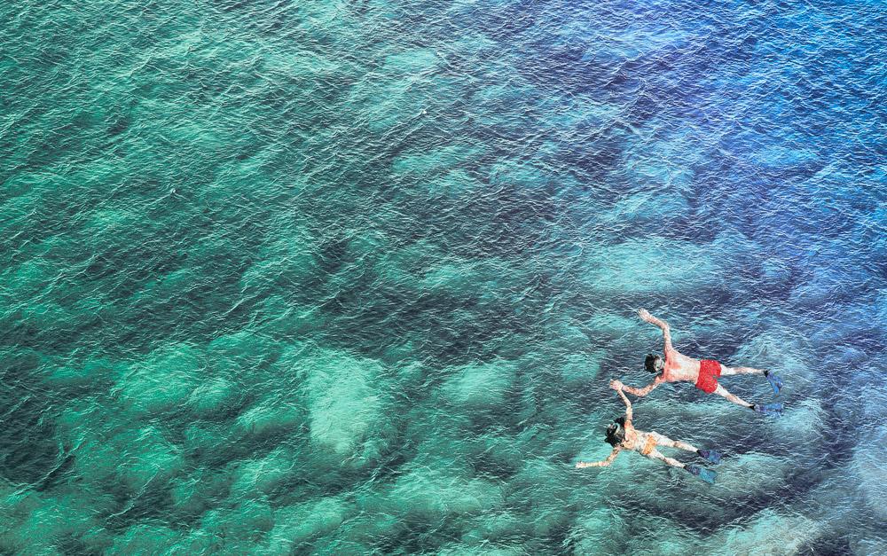 Duas pessoas nadando no mar