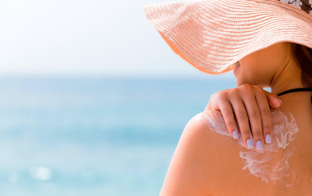 Mulher na praia aplicando o protetor solar nas costas