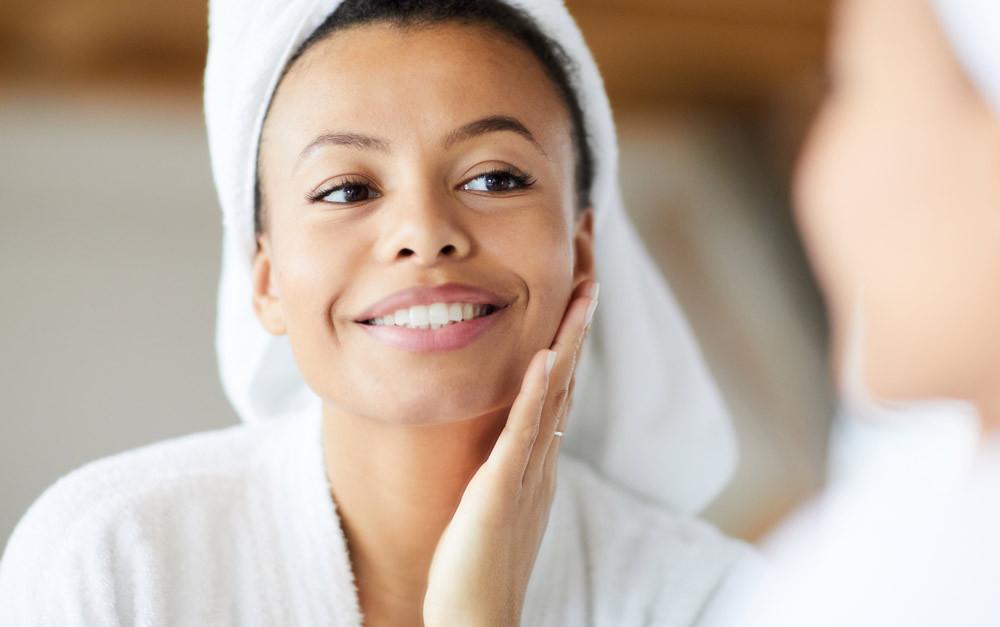 Mulher de toalha no cabelo passando creme no rosto