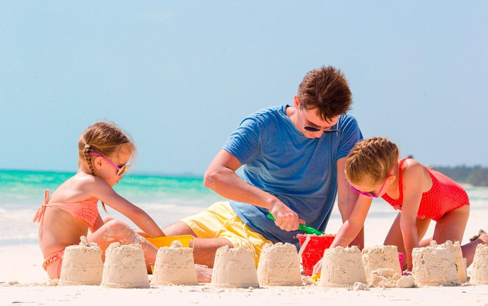 Homem com duas crianças na praia